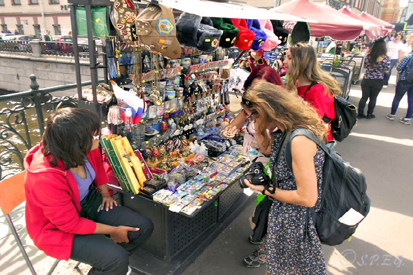 Tourists buying Russian souvenirs from a street market in St Petersburg, Russia.