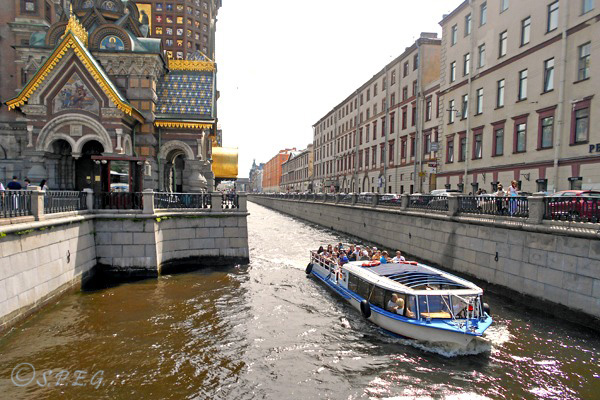 A boat tour cruising along the Griboyedov canal in St Petersburg, Russia.
