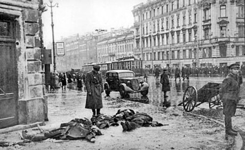 Photo taken during the Siege of Leningrad: a Russian man looking down at the dead bodies on the ground.